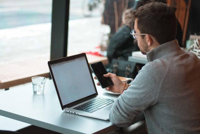 mężczyzna z telefonem przy laptopie